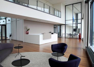 A contemporary reception lounge with white desk & reception chairs